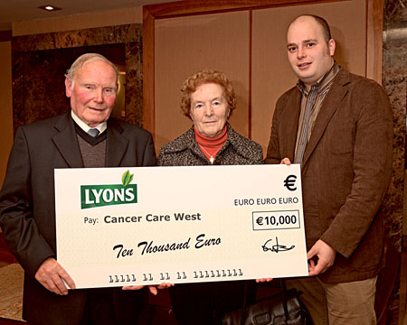 caption: James and Teresa Walsh from Westport presenting a cheque for €10,000 to David O'Donnell of Cancer Care West.