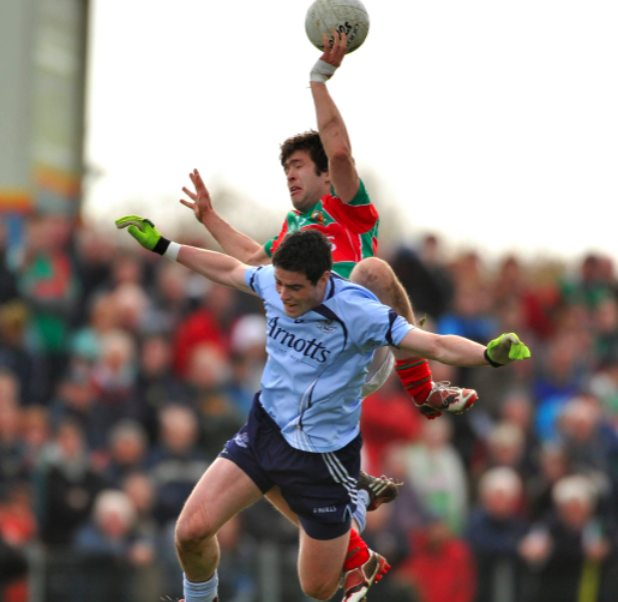 Pat Harte fly's high to win the ball against Ross McConnell in Ballina on Sunday. Photo: Sportsfile.