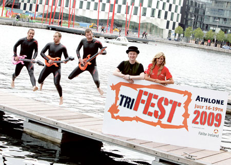 Musician Mundy who will play TriFest on Saturday July 18 is helped launch the Midland's festival with model Aoife Cogan and some guitar wielding men in wet suits!