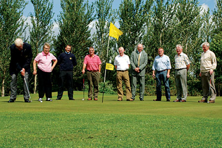 The Captain of Tuam Golf Club Mick O'Gara takes a putt on the new 10th green in the club in advance of next Sunday's official opening of the new club development. He is watched by Sr Agnes Curley (Lady Captain), John Davin, Sean Quinn, John G. Davin (President), Ian Pierce, Jerry Bradley (Secretary), Michael Niland, and Oliver Curley.