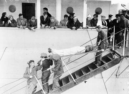 One of the survivors being lowered to the deck of the tender
