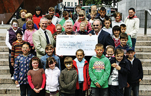 Pat Dillon (centre) of the Sunflower Chernobyl Appeal and children from Belarus visiting Galway recieve a cheque from Ciaran Hayes, director of transport and infrastructure at Galway City Council, and Liam Codd of West Ireland Cycling. Liam and his team raised the money in an event during Bike Week in June by hiring out bikes and selling smoothies made with machines powered by bikes. Photo:-Mike Shaughnessy