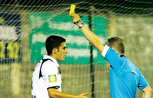 Galway United's Seamus Conneelly is booked by referee Anthony Buttime in action from the Airtricity League game at Terryland Park on Friday night.		 Photo:-Mike Shaughnessy