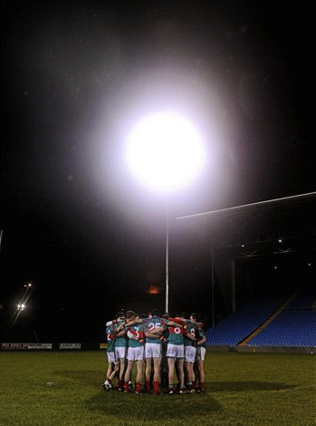 Ready for action: Mayo players gather in a huddle under the lights in McHale Park. Photo: Sportsfile