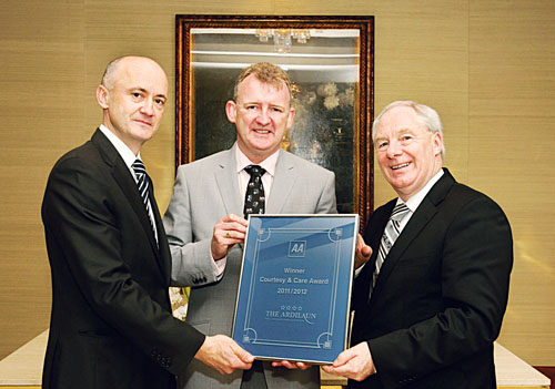 John Ryan of The Ardilaun hotel being presented with the award of AA Ireland Courtesy & Care Award by Minister of State at the Department of Transport, Tourism & Sport Michael Ring, and Brendan Nevin, CEO of AA Ireland.