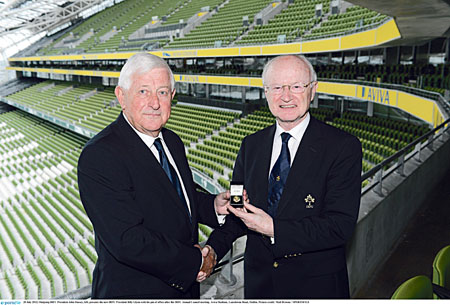 Outgoing IRFU president John Hussey, left, presents the new IRFU president Billy Glynn with his pin of office after the IRFU annual council meeting.