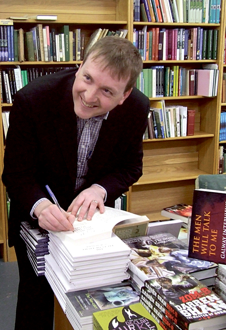 Cormac Ó Comhraí, co-editor of The Men Will Talk To Me – Galway Interviews, signing copies of the book in Kenny's recently.