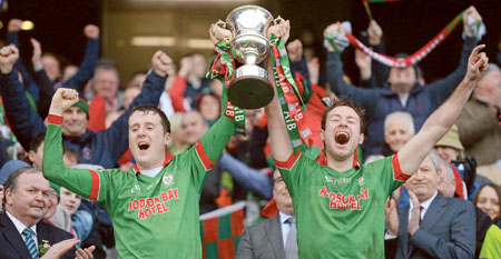 St Brigid's joint captains Gearóid Cunniffe, left, and Darragh Donnelly, lift the Andy Merrigan cup. Photo: SPORTSFILE