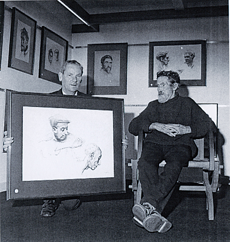 Des Kenny holding one of a series of sketches of Irish peasant faces, watched by the artist Seán Keating.