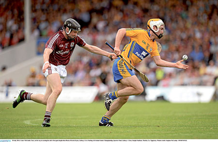 Conor McGrath, Clare, on his way to scoring his side's first goal despite the efforts of Kevin Hynes, Galway. Picture credit: Stephen McCarthy / SPORTSFILE