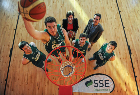 Moycullen Basketball's US player Michael Callaghan dunking the ball, watched by players Paul O'Brien, Eoghan Maxwell and Dylan Cunningham with Catherine Hannon and John O'Sullivan of new sponsors SSE Renewables.
