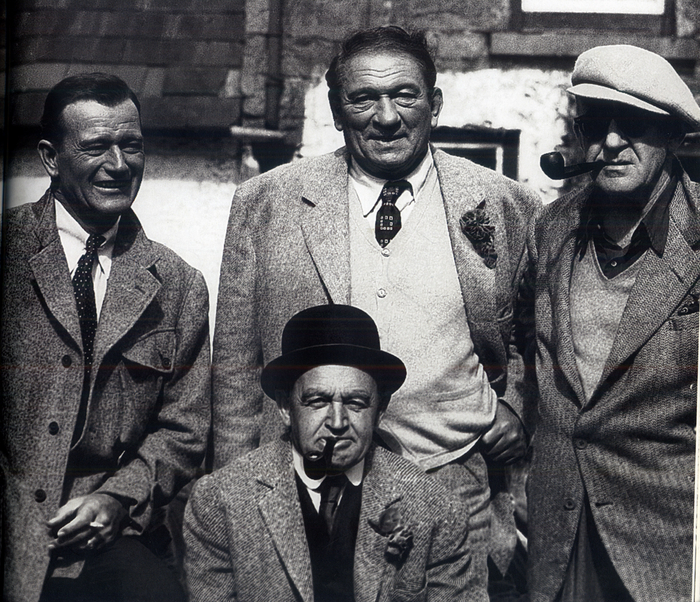 The perfect picture: John Wayne, Victor McLaglen, John Ford, and (sitting) Barry Fitzgerald all proudly wearing Irish tweeds made by Ó'Máille's for the film The Quiet Man.