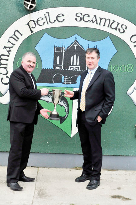 Thomas Welby presents the Welby Cup to Terence Monaghan, chairman of Cumann Peile Seamus O'Maille, Oughterard.	Photo: Tom Broderick