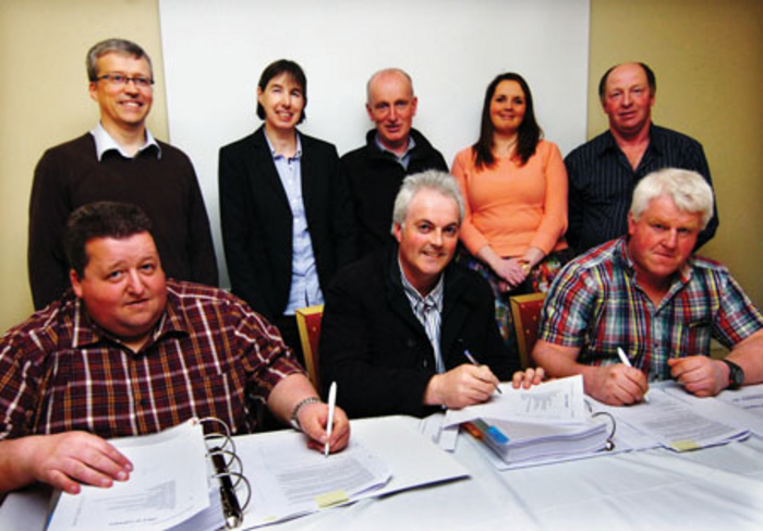 Peter Winters (centre) with Michael Cosgrove, treasurer RGWS, on left, and Tony Corduff, chairman, RGWS, signing the contracts for the Rossport Group Water Scheme upgrade.  Included at back are, from left: Alan Mee, SEPIL social performance manager, Aoife Carty, technical director, RPS; Thomas Gallagher, secretary, RGWS; Karina Carey, SEPIL senior accountant, and Michael T McGuinness, board member, RGWS.