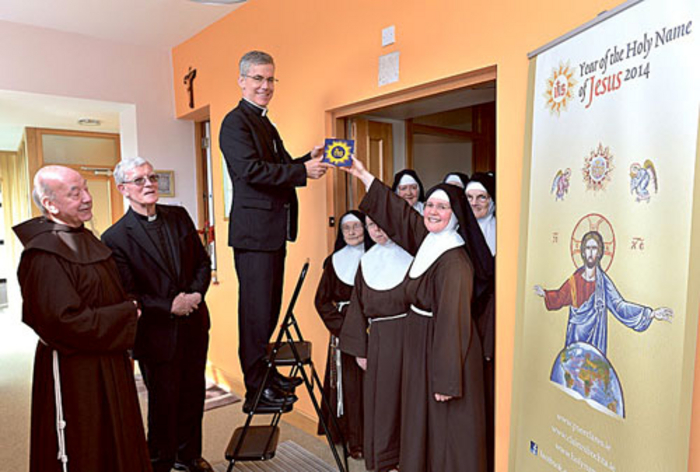 Sr Colette, Abbess of the Poor Clare community in Galway, hands one of the new range of Holy name tiles to Papal Nuncio, Archbishop Charles Brown, watched by Fr Fearghus OFM, Bishop Martin Drennan of Galway, and the Poor Clare sisters.
