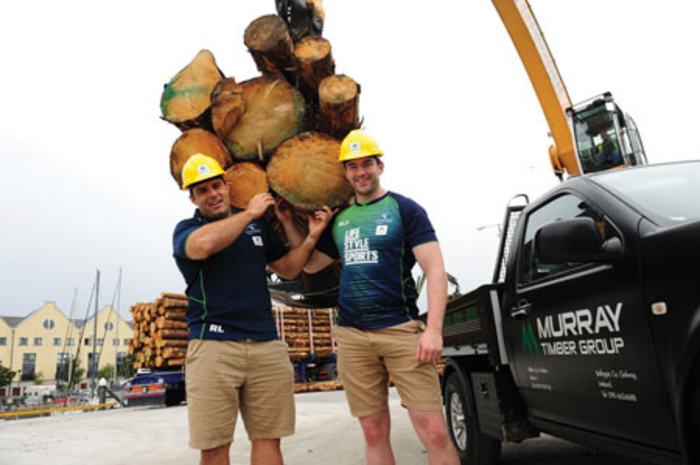 Connacht Rugby players Ronan Loughney and Andrew Browne lending a helping hand with the first logs shipment to come through Galway Harbour.
