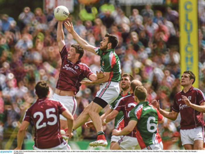 Gareth Bradshaw, Galway, in action against Kevin McLoughlin, Mayo, as their teammates await the breaking ball.