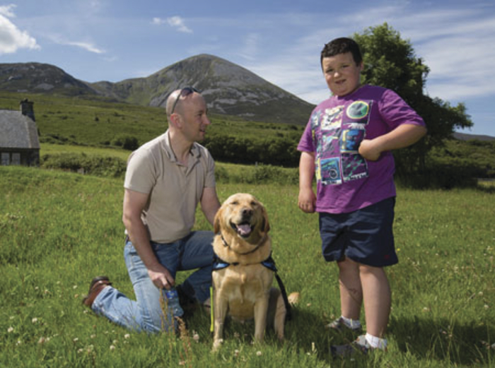 Brian Galvin with his son Adam and their assistance dog Nikita, whose constant companionship has transformed their family life.