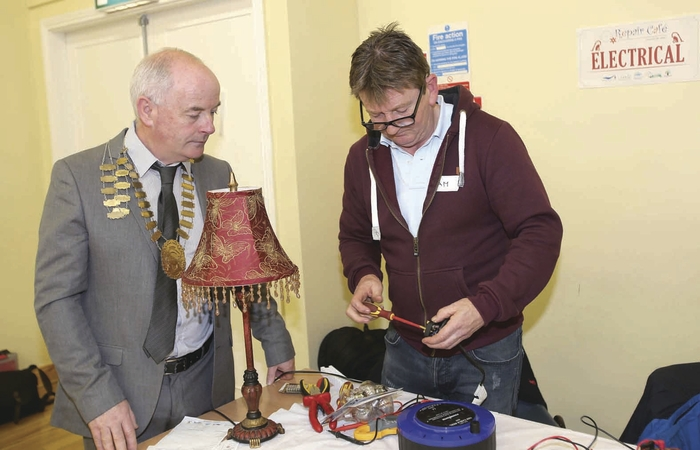 Cllr Frankie Keena watches as Liam Macken repairs his lamp at Athlone's first Repair Café