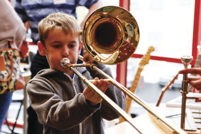 A young library user gets to grips with a trombone at the launch of the county's first music bank in Castlebar Library.