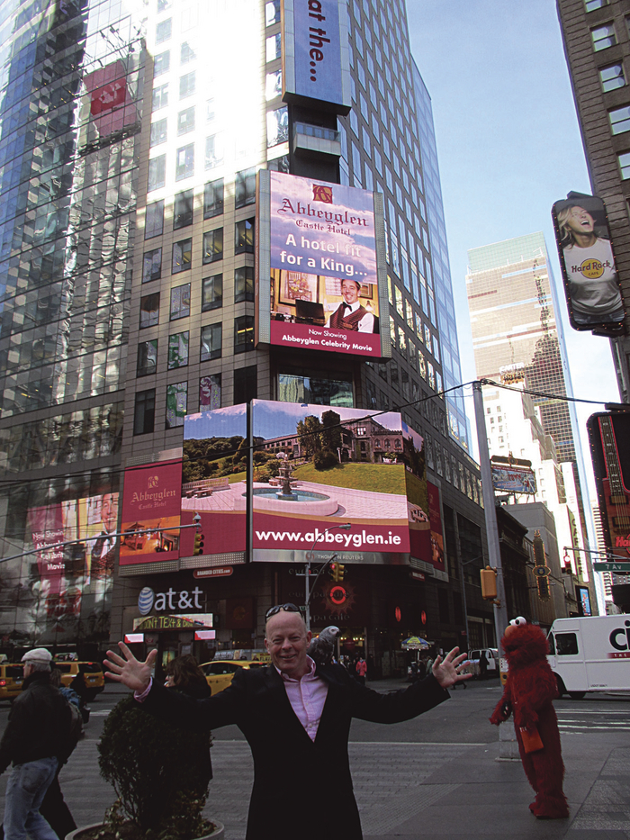 Brian Hughes pictured in front of the ad at Times Square.