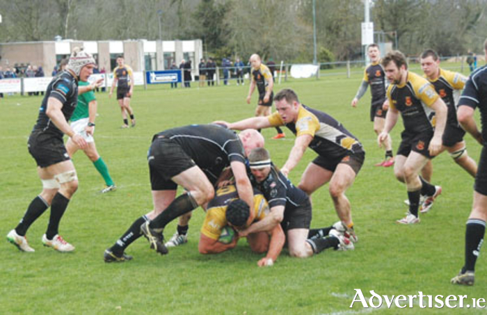 Buccaneers' Ronan Farrell tries to burrow through the tackles of Ballymena duo Ian Caldwell and William McKay
