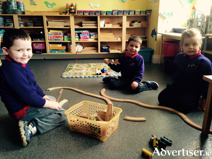 Aaron, Daniel, and Roisin building a train track together at Amy's House Creche.