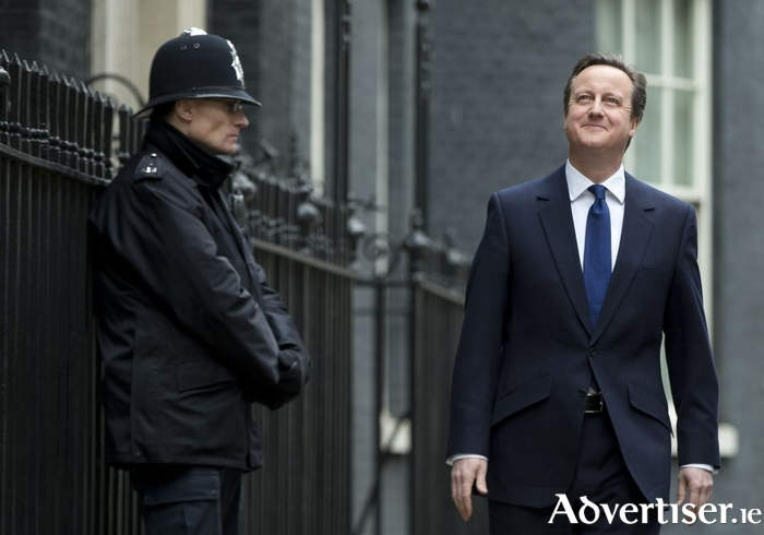 UK prime minister David Cameron walks along Downing Street, while a British bobby watches on.