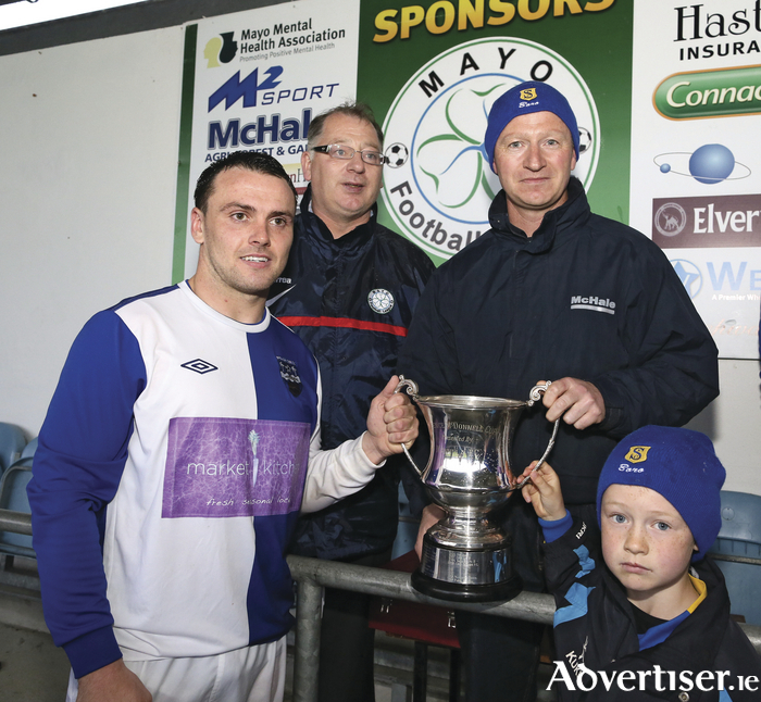 Daniel Helly, captain Ballina Town  raises the Terence McDonnell Cup after defeating Ballyglass in the McDonnell Cup Final (sponsored by McHale Agri Forest and Garden) in Milebush Park. Photo: Michael Donnelly