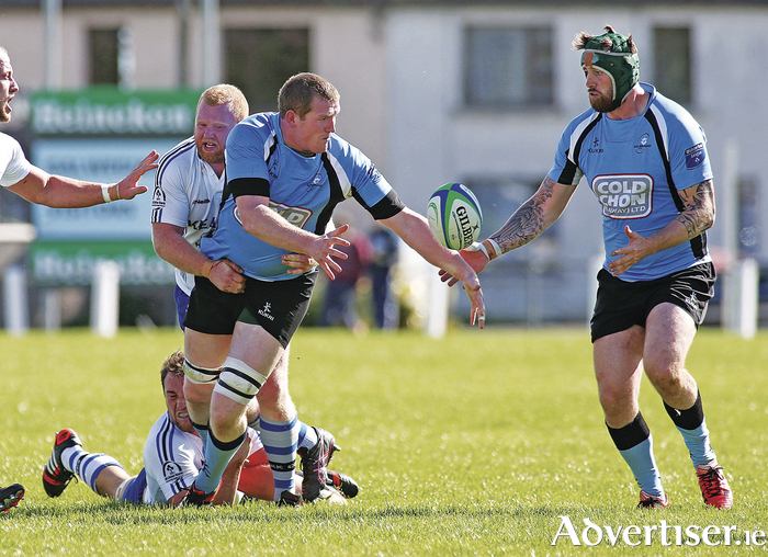 Marty Cummins of Galwegians, tackled by Cork Constitution's Ger Seweeny, offloads to Aly Muldowney in Galwegians opening day victory in  the Ulster Bank All Ireland Leaguedivision 1A  at Crowley Park.       Photograph: Mike Shaughnessy