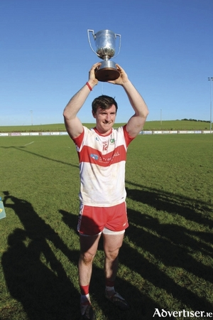 Champions: Cathal Freeman lifts the trophy after Aghamore pick up the Division 1B title. Photo: Aghamore GAA