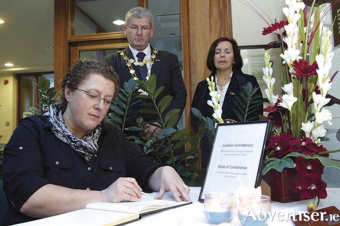 In the wake of the Paris terrorist attack Catherine Gagneux the French honorary consul to Galway signs the book of condolence at City Hall on Monday morning  observed by Mayor Frank Fahy and Marie-Héléne Poudevigne French Counsular Councillor. Photo:-Mike Shaughnessy