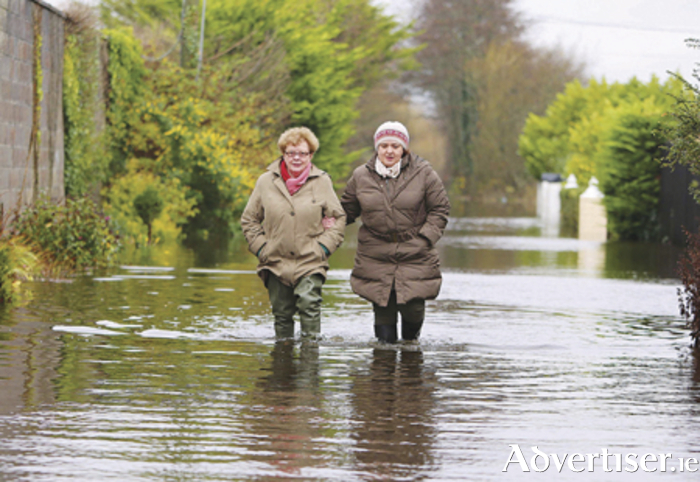 Breda Caulfield leaves her flooded home at Clonown Road, Athlone with the help of her daughter Rosemarie Photo: Hany Marzouk