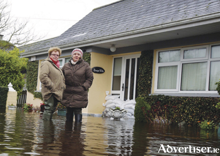Breda Caulfield leaving her home with the help of her daughter Rosemarie at Clonown Road, Athlone after it was flooded  Photo: Hany Marzouk