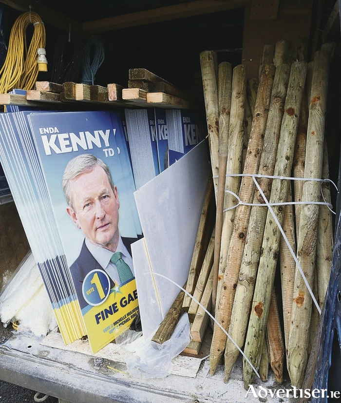 From the van to the pole: Campaign workers were busy putting up election posters this week. Photo: Michael Donnelly