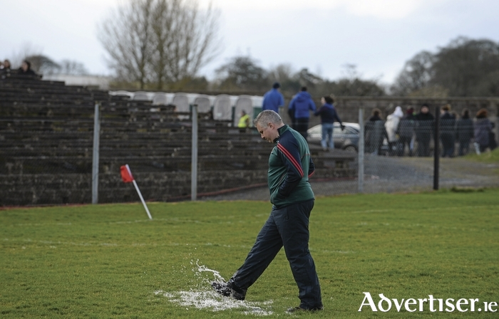 Kicking ahead: Stephen Rochford kicks one of the puddles on the pitch ahead of throw-in on Sunday. Photo: Sportsfile