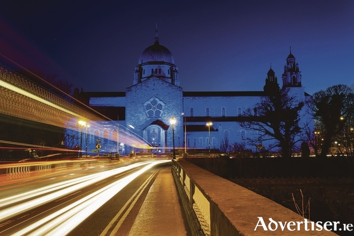 Galway Cathedral lit up blue at night and car lights trails