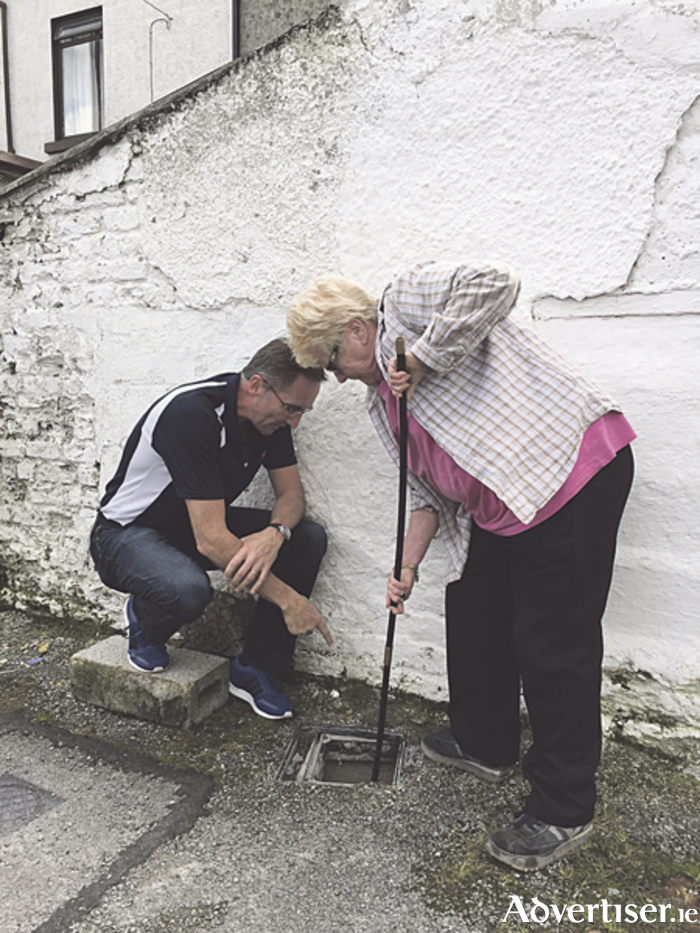 Cllr Aengus O'Rourke helping Mrs Cleary deal with yet another blockage