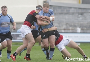 Galwegians Jack Dinneen is tackled by UCC's Charlie O'Regan and Conor  Barry in action from the Ulster Bank, AIL Division 1A game at Crowley Park on Saturady. Photo:-Mike Shaughnessy