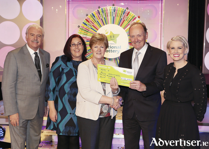 Mary O' Donnell from Castlebar has won €30,000 including a holiday to Dubai on last Saturday's National Lottery Winning Streak game show on RTE.  Pictured here at the presentation of the winning cheques were from left to right: Marty Whelan, Caroline Geraghty, (who played on behalf of her mother), Mary O'Donnell, Declan Harrington (head of finance at the National Lottery), and Sinead Kennedy. The winning ticket was bought from Newstand, Market Square, Castlebar. Photo: Mac Innes Photography.