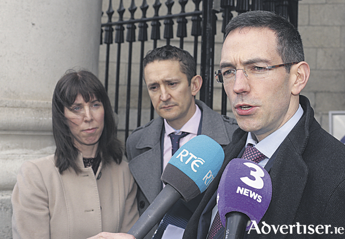 Solicitor for the Farrells, Roger Murray (R), speaking to the media on Tuesday after the case, while Niamh and Shane Farrell, parents of Sadhbh Farrell (6), of Killeeneen, Craughwell, Co. Galway, look on. Photo: Courtpix
