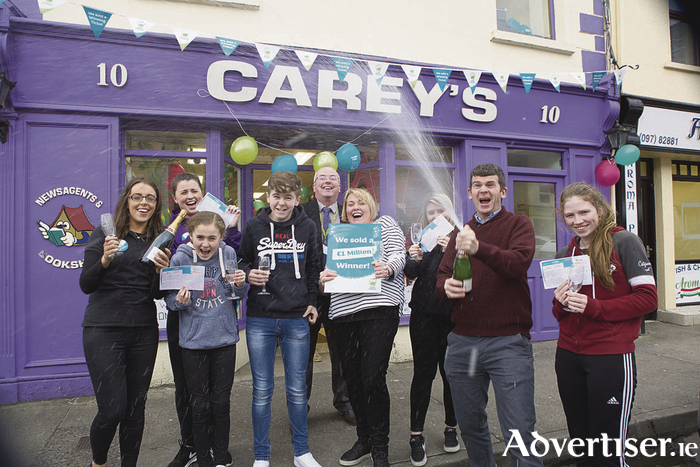 Celebration time. Lorraine Carey (centre, striped top)  is pictured celebrating the sale of the winning ticket with staff from her shop this afternoon last Friday.