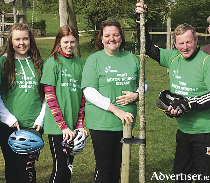 Taoiseach Enda Kenny recently took part in the 'Tour of the Lakelands Cycle Challenge' in memory of the late Nicky McFadden TD and to raise funds for and awareness of Motor Neurone disease. He is pictured with Kate O'Connell, Rachel Barrington, and Senator Gabrielle McFadden revisiting a tree that he planted in honour of Nicky last year in Dún na Sí Heritage Park, Moate.