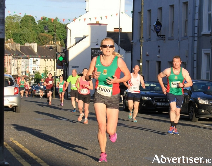 Angela McVann (Mayo AC)  leads a group along Upper Main St at the Ballyhaunis 5km on Tuesday evening.