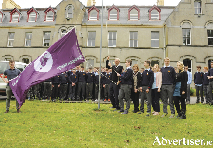 Micheal O Muircheartaigh on a recent visit to St Muredach's College raised The Gaelbhratach Flag. The college was awarded this flag for its efforts in promoting the Irish language within the school. Left to right: Sean Gaughan, Micheal O'Muircheartaigh, Conor Clarke, Angela Lavelle, Niall Judge, Sile Mc Andrew, Kenneth Healy and Maria Ní Bhedláin. Photo: John O'Grady.