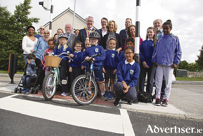 Galway City Mayor Pearce Flannery, councillors Donal Lyons and Niall McNelis, and school principal Noreen Healy with parents and students from St John the Apostle Knocknacarra National School at the recently lit pedestrian crossing at Bóthar Stiofán, Western Distributor Road, Knocknacarra, near the school entrance. Photo: Brian Harding