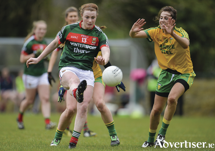 Getting a shot off: Aileen Gilroy kicks for a point despite the efforts of Roisin Friel during Mayo's league meeting with Donegal in April. Photo: Sportsfile.