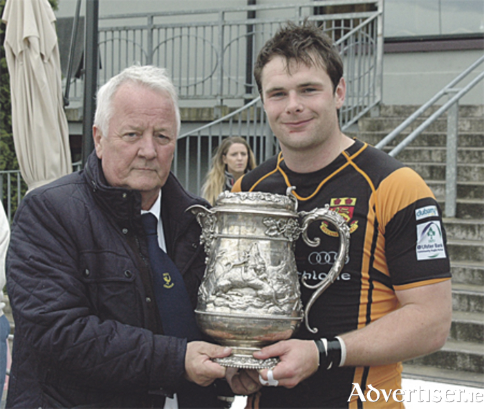 Shane Layden of Buccs is presented with the Connacht Senior League trophy by Ted Carty, Connacht junior vice-president