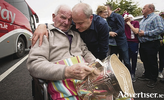 Galway manager Micheal Donoghue shows the Liam McCarthy to his father Miko Donoghue for the first time, in Ballinasloe.