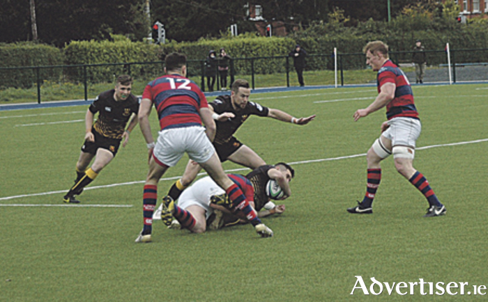 Thomas McGann retains possession for Buccaneers despite James Downey of Clontarf's tackle